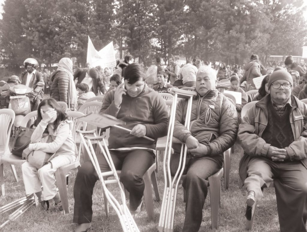 Picture of  people with various kind of disabilities sitting at the front row of a program