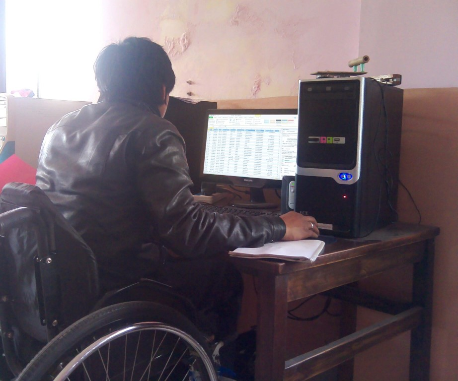 a person in a wheelchair at his workdesk