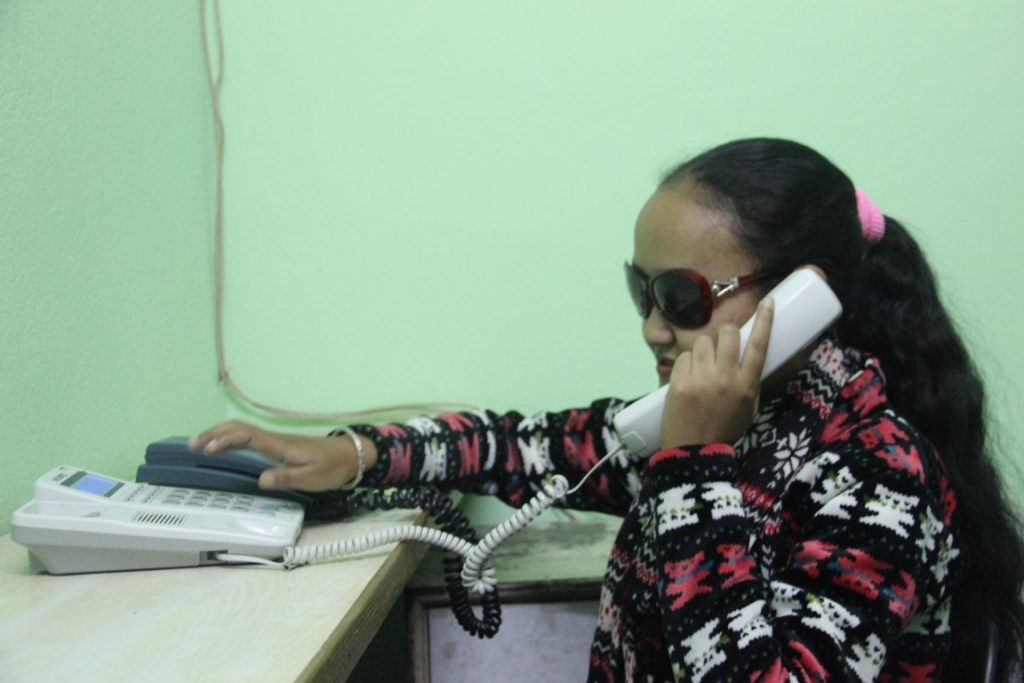 a visually impaired girl speaking on telephone in her office