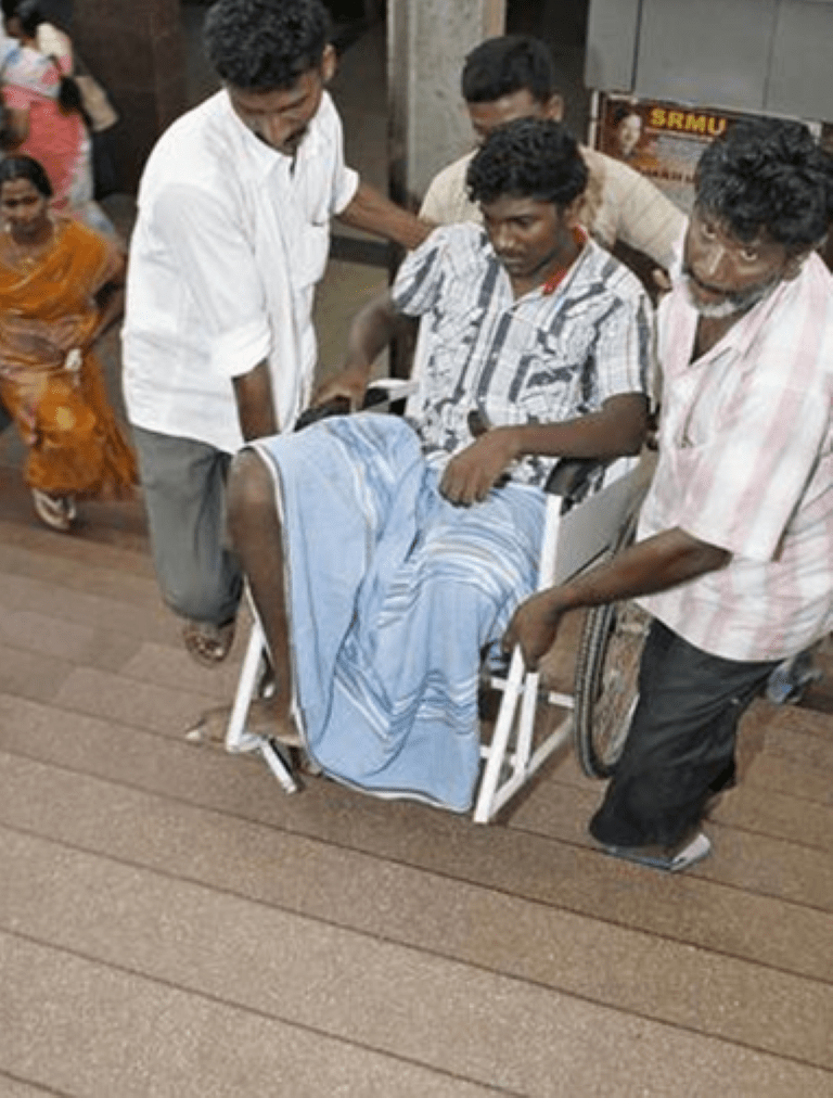 A wheelchair user being carried in stairs