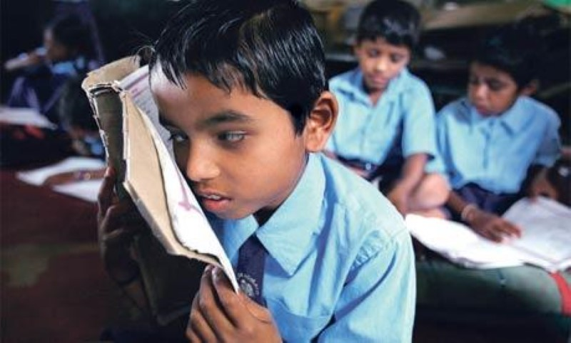 a child with low vision reading a book by bringing it closer to his eyes.