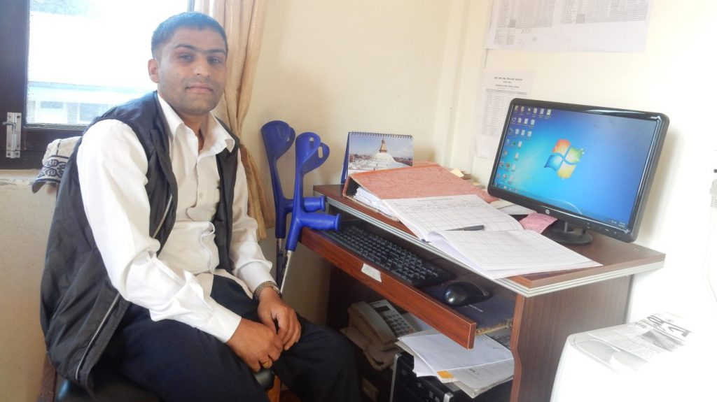 a person at his workdesk. His workdesk contains a computer and other papers